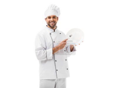 handsome young chef with plate and fork looking at camera isolated on white