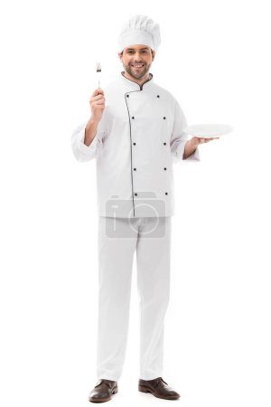 Photo for Happy young chef with plate and fork looking at camera isolated on white - Royalty Free Image