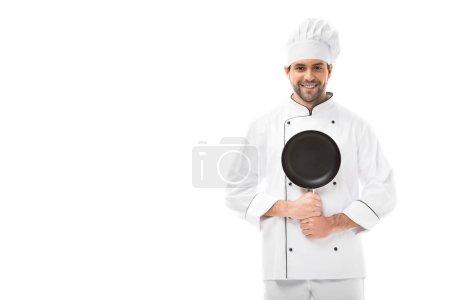 Photo pour Heureux jeune chef tenant poêle et regardant caméra isolé sur blanc - image libre de droit