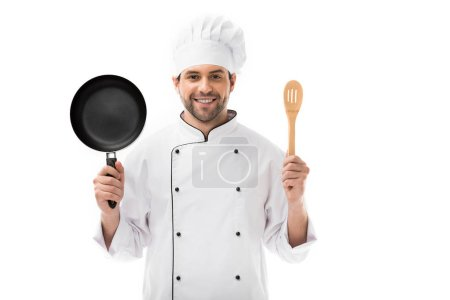 Photo for Happy young chef holding frying pan and wooden spatula isolated on white - Royalty Free Image