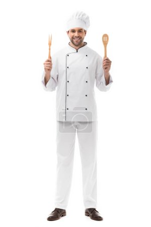 Photo for Smiling young chef holding kitchen utensils and looking at camera isolated on white - Royalty Free Image
