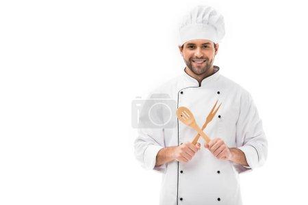 Photo pour Heureux jeune chef tenant ustensiles de cuisine en bois et regardant caméra isolé sur blanc - image libre de droit