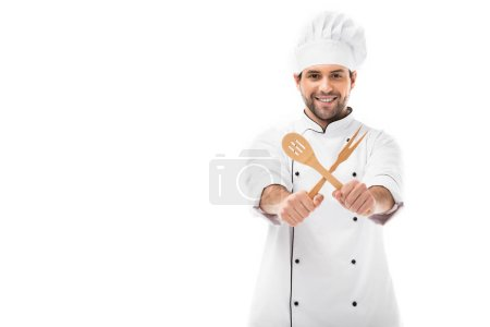 Photo for Smiling young chef holding wooden kitchen utensils and looking at camera isolated on white - Royalty Free Image