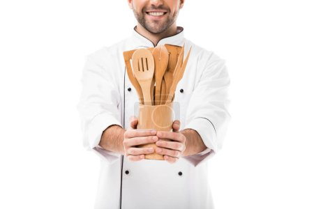 cropped shot of smiling young chef with bunch of wooden kitchen utensils isolated on white