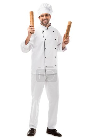smiling young chef holding bamboo pepper mills isolated on white