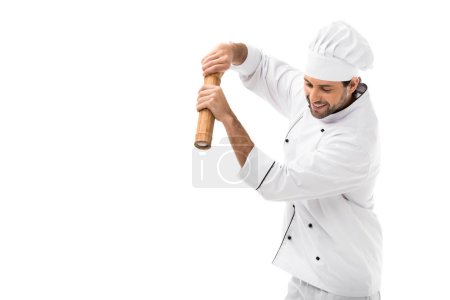 smiling young chef with bamboo pepper mill isolated on white