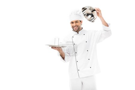 smiling young chef opening seving dome with glass of water inside isolated on white