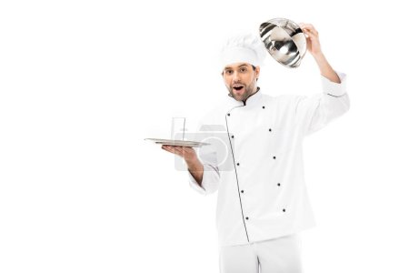 surprised young chef opening seving dome with glass of water inside isolated on white