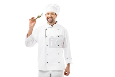 smiling young chef holding bunch of thymes and looking at camera isolated on white