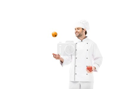 smiling young chef juggling with tomato and bell pepper isolated on white
