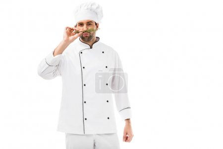 handsome young chef making mustache with thymes and looking at camera isolated on white