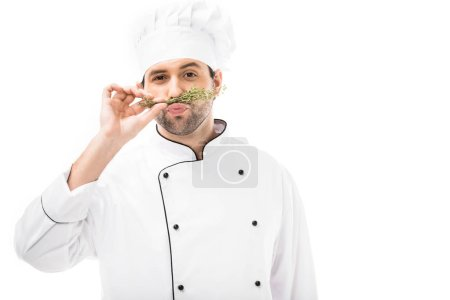 funny young chef making mustache with thymes and looking at camera isolated on white