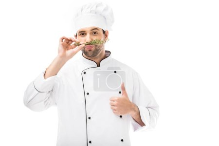handsome young chef making mustache with thymes and showing thumb up isolated on white