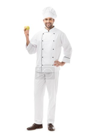 Photo for Full length view of handsome young chef holding fresh apple and smiling at camera isolated on white - Royalty Free Image