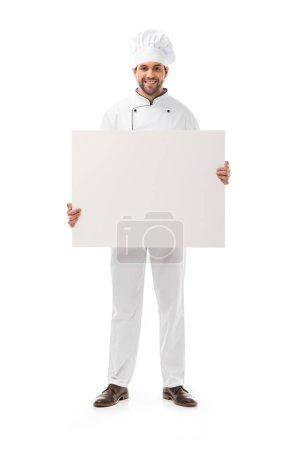 full length view of handsome male cook holding blank placard and smiling at camera isolated on white