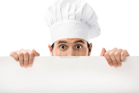 Photo for Professional male cook peering out blank banner and looking at camera isolated on white - Royalty Free Image