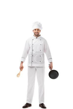 professional young chef holding utensils above head and smiling at camera isolated on white