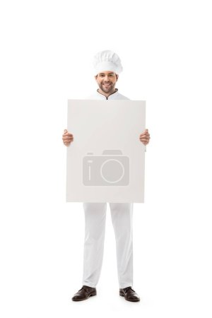 handsome young chef holding blank banner and smiling at camera isolated on white