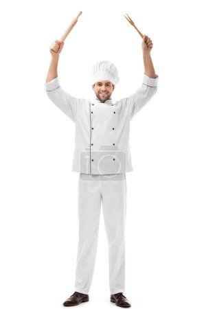 handsome young chef holding utensils above head and smiling at camera isolated on white