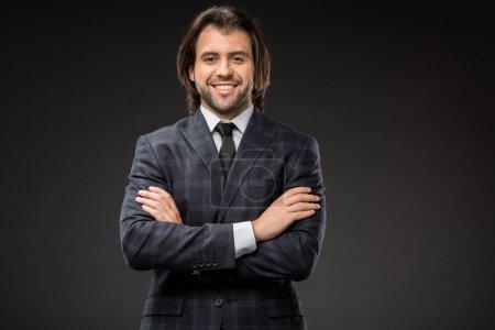 Foto de Apuesto hombre de negocios feliz de pie con los brazos cruzados y sonriendo a cámara aislada en negro - Imagen libre de derechos