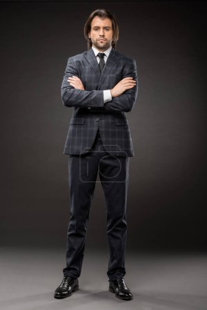hombre de negocios seguro de pie con los brazos cruzados y mirando a la cámara en negro
