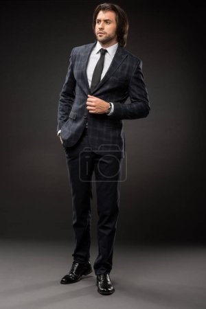full length view of professional serious businessman in stylish suit looking away on black