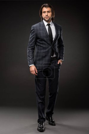 full length view of professional businessman in stylish suit standing with hand in pocket on black