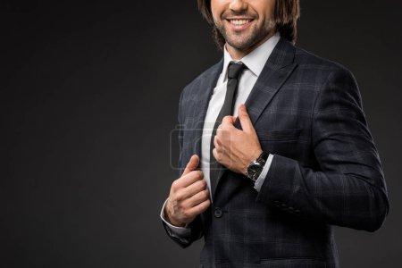 cropped shot of smiling businessman wearing stylish suit jacket isolated on black