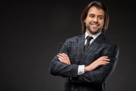 handsome smiling young businessman standing with crossed arms and looking away isolated on black