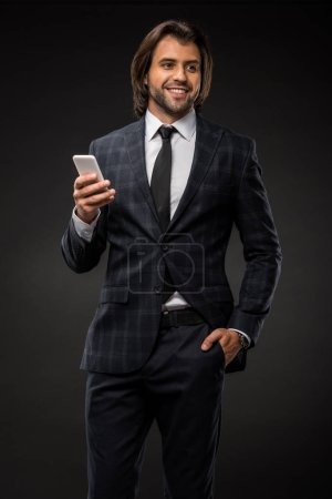 smiling young businessman standing with hand in pocket and holding smartphone isolated on black