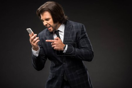 emotional young businessman screaming at smartphone isolated on black