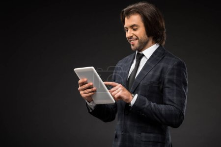 Photo for Professional smiling young businessman using digital tablet isolated on black - Royalty Free Image