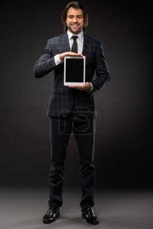 handsome young businessman holding digital tablet with blank screen and smiling at camera on black