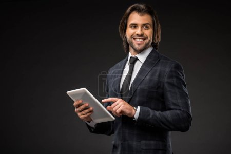 smiling young businessman using digital tablet and looking away isolated on black