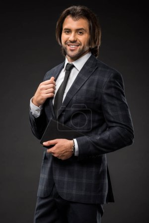 Photo pour Bel homme d'affaires professionnel tenant un bloc-notes et souriant à la caméra isolé sur noir - image libre de droit