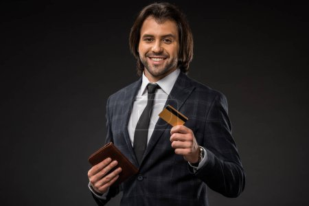 smiling young businessman holding wallet and credit card isolated on black