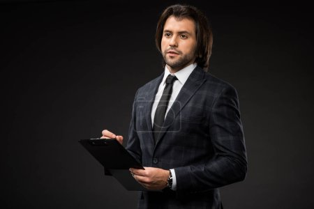 serious young businessman writing on clipboard and looking away isolated on black