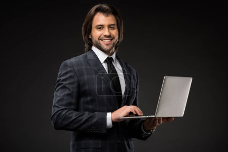 handsome young businessman using laptop and smiling at camera isolated on black