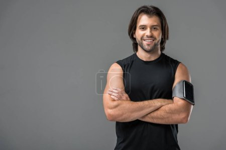 Photo for Athletic young man with armband and smartphone standing with crossed arms and smiling at camera isolated on grey - Royalty Free Image