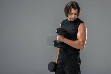 Photo for Muscular handsome man training with dumbbells and looking at biceps isolated on grey - Royalty Free Image