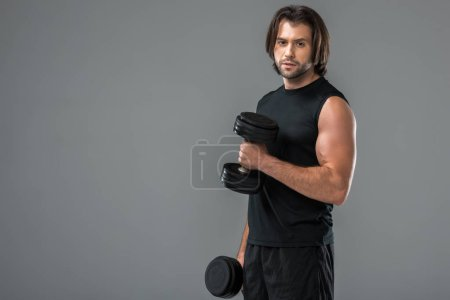 Photo for Muscular young man exercising with dumbbells and looking at camera isolated on grey - Royalty Free Image