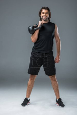 Photo for Full length view of athletic young man exercising with kettlebell and smiling at camera on grey - Royalty Free Image