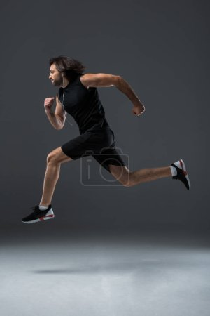 side view of athletic man in earphones running and jumping on grey