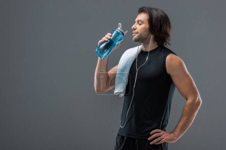 smiling muscular man with towel drinking water from sports bottle isolated on grey