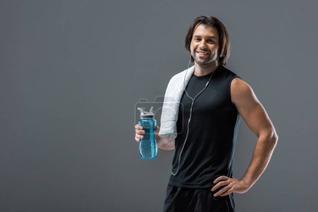 handsome young sportsman in earphones holding bottle of water and smiling at camera isolated on grey