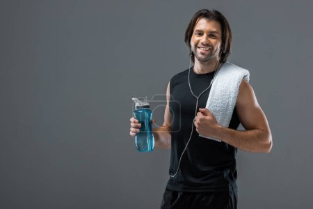 happy young sportsman in earphones holding bottle of water and smiling at camera isolated on grey