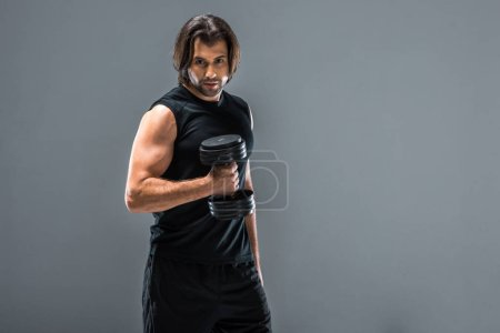 handsome athletic man holding dumbbell and looking at camera isolated on grey