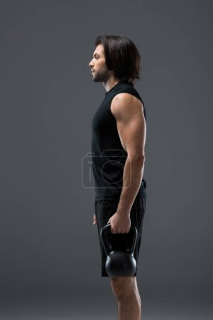 Photo for Side view of athletic man holding kettlebell and looking away isolated on grey - Royalty Free Image