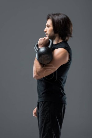 Photo for Side view of muscular young man exercising with kettlebell isolated on grey - Royalty Free Image