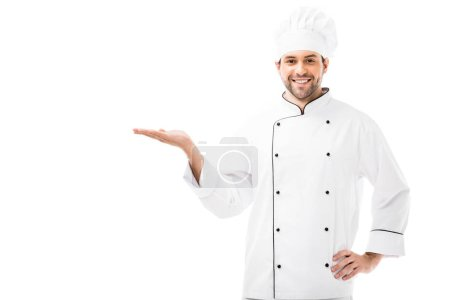 handsome young chef showing copy space and smiling at camera isolated on white